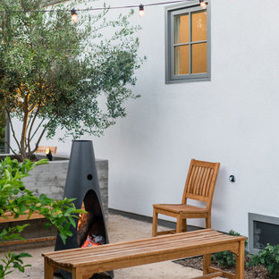 This is an example of a mid-sized contemporary backyard patio in Los Angeles with a fire feature, decomposed granite and no cover.