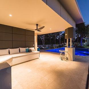 Immagine di un ampio patio o portico minimal dietro casa con graniglia di granito e un tetto a sbalzo