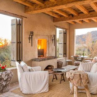 Idee per un patio o portico stile americano con un focolare, pavimentazioni in mattoni e un tetto a sbalzo