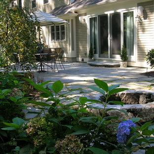 Idee per un piccolo patio o portico classico dietro casa con un focolare, pavimentazioni in pietra naturale e nessuna copertura
