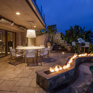 Large island style backyard concrete paver patio photo in Los Angeles with a fire pit and a roof extension