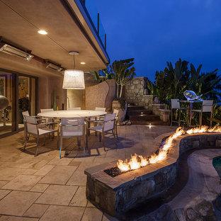 Idée de décoration pour une grande terrasse arrière ethnique avec un foyer extérieur, une extension de toiture et des pavés en béton.
