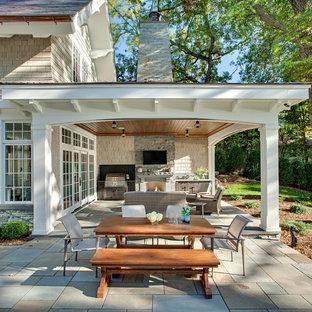 Cette photo montre une terrasse arrière chic avec des pavés en pierre naturelle, une extension de toiture et une cheminée.