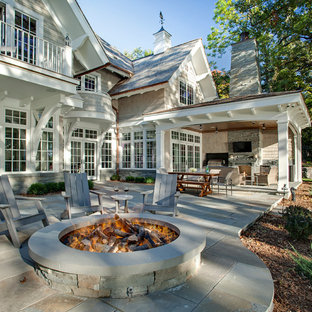 Elegant backyard stone patio kitchen photo in Minneapolis with a roof extension