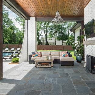 Immagine di un patio o portico country di medie dimensioni e dietro casa con un tetto a sbalzo e piastrelle