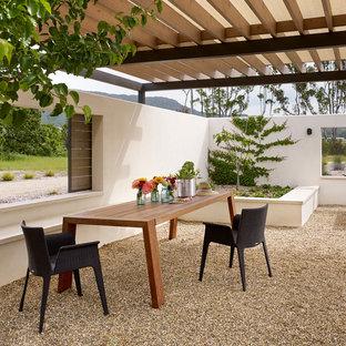 Esempio di un patio o portico country con ghiaia e una pergola