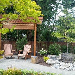 Immagine di un grande patio o portico etnico dietro casa con fontane, una pergola e cemento stampato