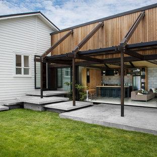 Ispirazione per un patio o portico industriale dietro casa con lastre di cemento e un parasole