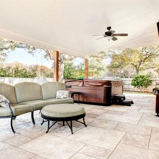 Immagine di un grande patio o portico design dietro casa con cemento stampato e un tetto a sbalzo