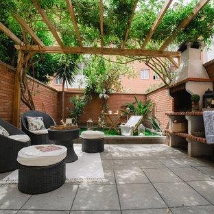 Imagen de patio clásico renovado con cocina exterior, adoquines de hormigón y cenador