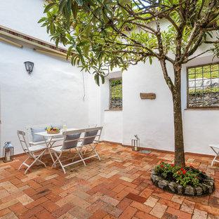 Foto di un patio o portico mediterraneo di medie dimensioni e dietro casa con un giardino in vaso, pavimentazioni in mattoni e nessuna copertura
