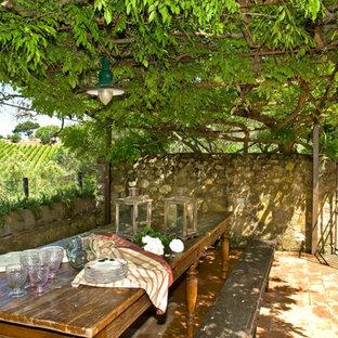 Immagine di un patio o portico country davanti casa con pavimentazioni in mattoni e una pergola