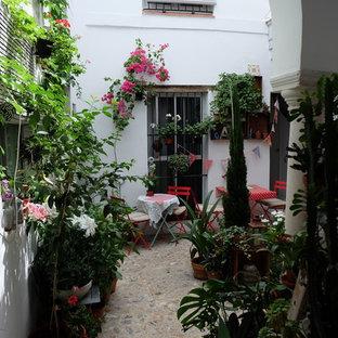 Cette image montre une grande terrasse et balcon style shabby chic avec des pavés en pierre naturelle et aucune couverture.