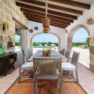 Idee per un patio o portico mediterraneo nel cortile laterale con piastrelle e un tetto a sbalzo