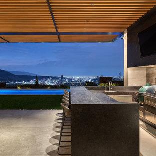 Immagine di un grande patio o portico contemporaneo dietro casa con un tetto a sbalzo