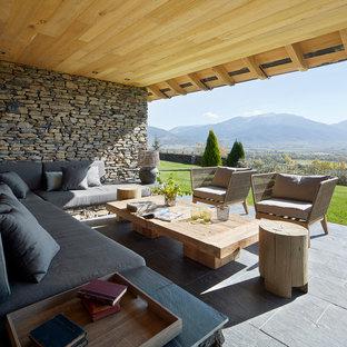 Immagine di un patio o portico country dietro casa con pavimentazioni in pietra naturale e un tetto a sbalzo