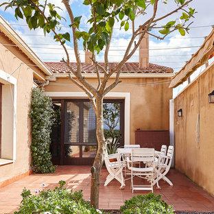 Неиссякаемый источник вдохновения для домашнего уюта: маленький дворик на боковом дворе в средиземноморском стиле с растениями в контейнерах и покрытием из плитки без защиты от солнца