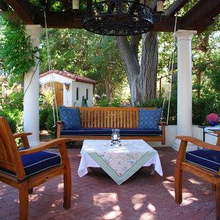 Immagine di un grande patio o portico mediterraneo dietro casa con pavimentazioni in mattoni e un gazebo o capanno