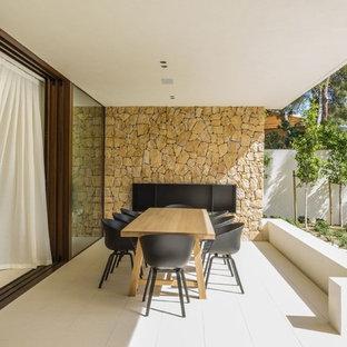 Modelo de patio mediterráneo, en anexo de casas, con chimenea y suelo de baldosas