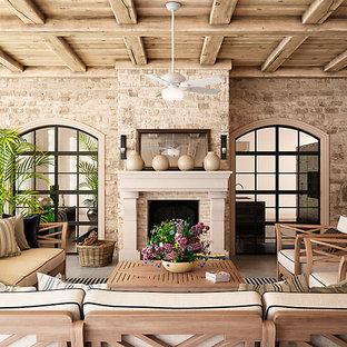 Immagine di un grande patio o portico chic con un tetto a sbalzo e un caminetto