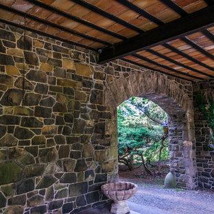 Foto di un patio o portico vittoriano di medie dimensioni e dietro casa con pavimentazioni in pietra naturale e un tetto a sbalzo