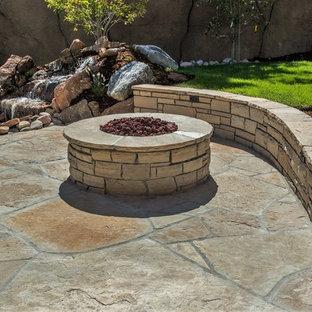 Ispirazione per un grande patio o portico rustico dietro casa con un focolare e pavimentazioni in pietra naturale