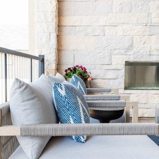 Immagine di un patio o portico minimal di medie dimensioni e dietro casa con un caminetto e un tetto a sbalzo