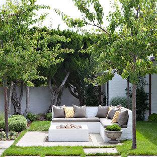Idee per un patio o portico costiero dietro casa con un focolare, pavimentazioni in cemento e nessuna copertura