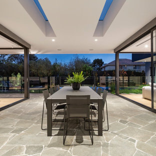 Contemporary patio in Melbourne with natural stone pavers and a roof extension.