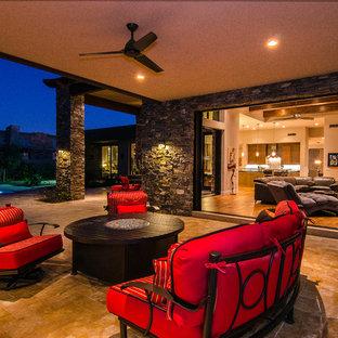 Idee per un patio o portico design con un focolare, piastrelle e un tetto a sbalzo