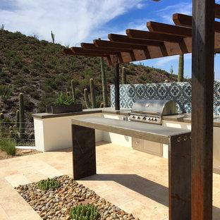 Patio kitchen - large southwestern backyard stone patio kitchen idea in Phoenix with a pergola