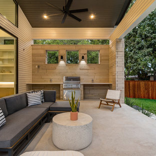 Inspiration for a mid-sized scandinavian backyard concrete patio kitchen remodel in Austin with a roof extension