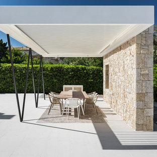 Imagen de patio mediterráneo, grande, en patio delantero, con losas de hormigón y pérgola
