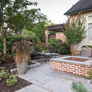 Idee per un piccolo patio o portico industriale dietro casa con un focolare, pavimentazioni in pietra naturale e nessuna copertura