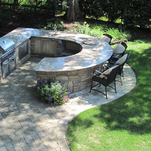 Inspiration for a timeless backyard stone patio kitchen remodel in New York
