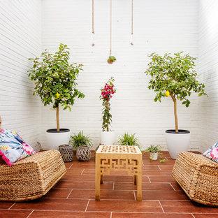 Ispirazione per un patio o portico mediterraneo di medie dimensioni e nel cortile laterale con un giardino in vaso