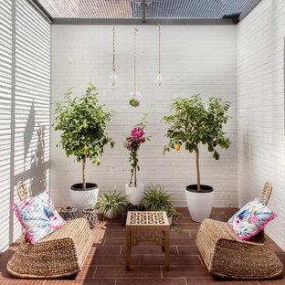 Immagine di un piccolo patio o portico mediterraneo in cortile con un giardino in vaso