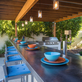 This is an example of a large contemporary back patio in Phoenix with an outdoor kitchen, tiled flooring and an awning.