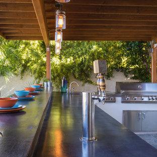 Immagine di un grande patio o portico industriale dietro casa con piastrelle e un parasole