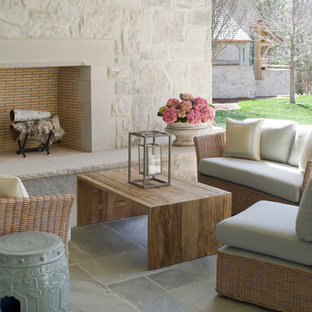 Inspiration for a timeless stone patio remodel in Charlotte with a fireplace