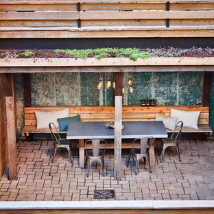 Mid-sized mountain style backyard brick patio kitchen photo in New York with a roof extension