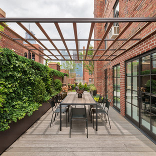 Photo of a large contemporary patio in New York with an awning, a living wall and decking.