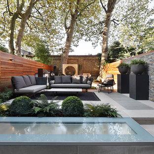 Foto de patio actual, de tamaño medio, en patio trasero, con jardín de macetas y adoquines de piedra natural