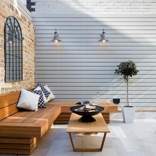 Esempio di un piccolo patio o portico chic dietro casa con un focolare e pavimentazioni in pietra naturale