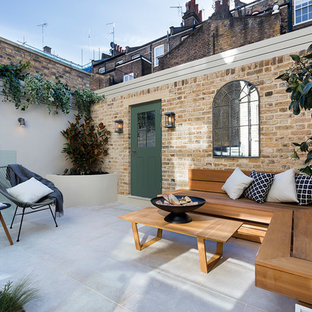 This is an example of a small classic back patio in London with a fire feature, concrete paving and no cover.