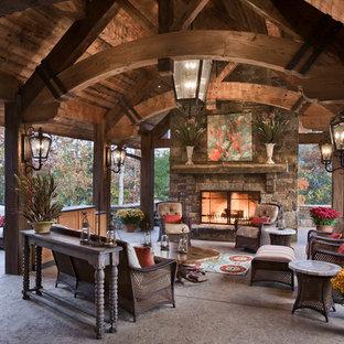 Ispirazione per un patio o portico stile rurale con un focolare