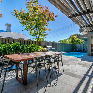 Contemporary backyard patio in Geelong with concrete pavers and an awning.