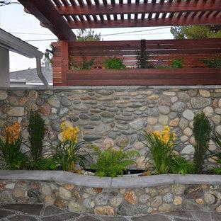 Foto di un piccolo patio o portico etnico dietro casa con un focolare, pavimentazioni in pietra naturale e una pergola