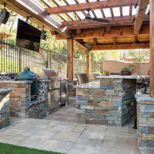 Patio kitchen - mid-sized transitional backyard stone patio kitchen idea in Orange County with a pergola
