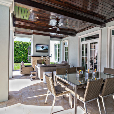 Inspiration for a large transitional backyard tile patio remodel in Miami with a fire pit and a roof extension